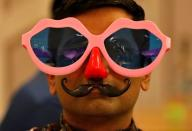 A man wearing a pair of goggles and plastic nose and mustache looks on during a party to celebrate the arrival of the New Year inside a hotel in Ahmedabad