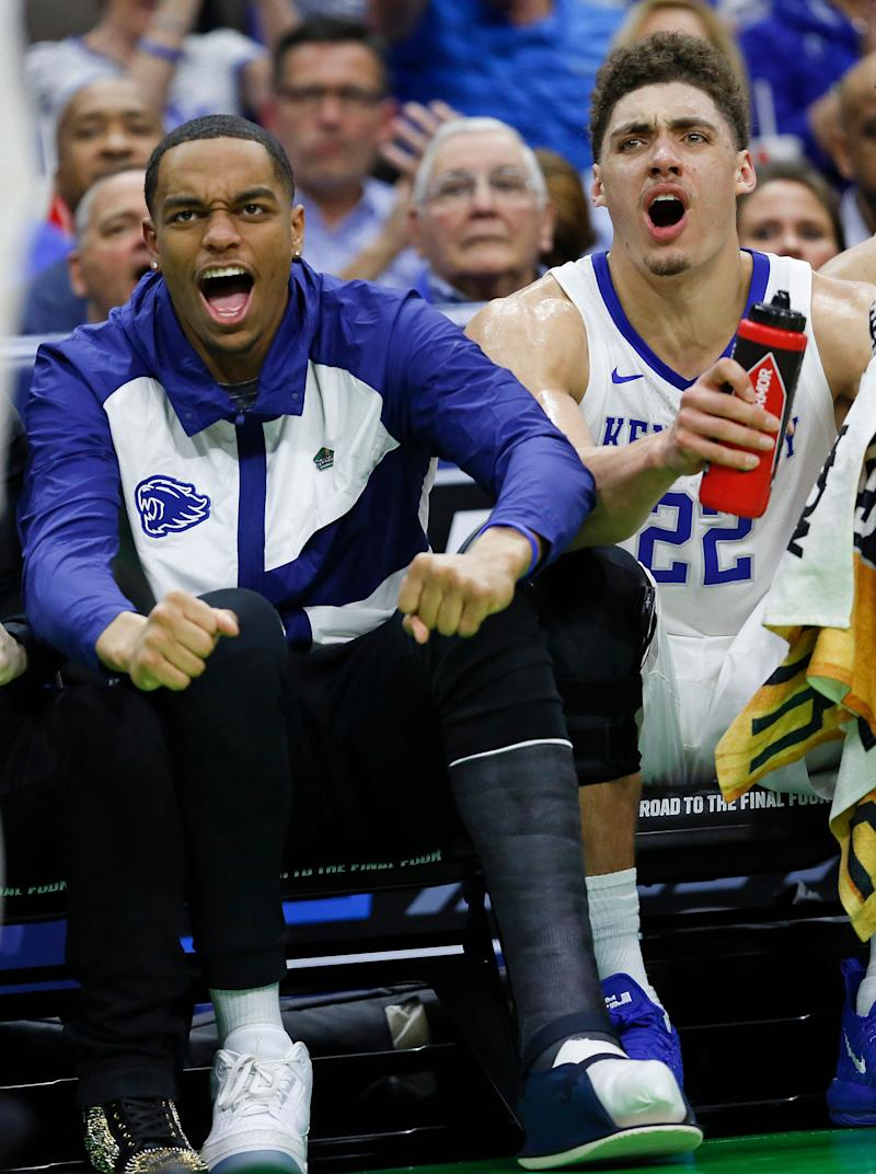 Kentucky's PJ Washington, left, wearing a cast on his left foot, and Reid Travis (22) cheer for their team during the second half against Abilene Christian in a first-round game in the NCAA men's college basketball tournament Thursday, March 21, 2019, in Jacksonville, Fla. (AP Photo/Stephen B. Morton)