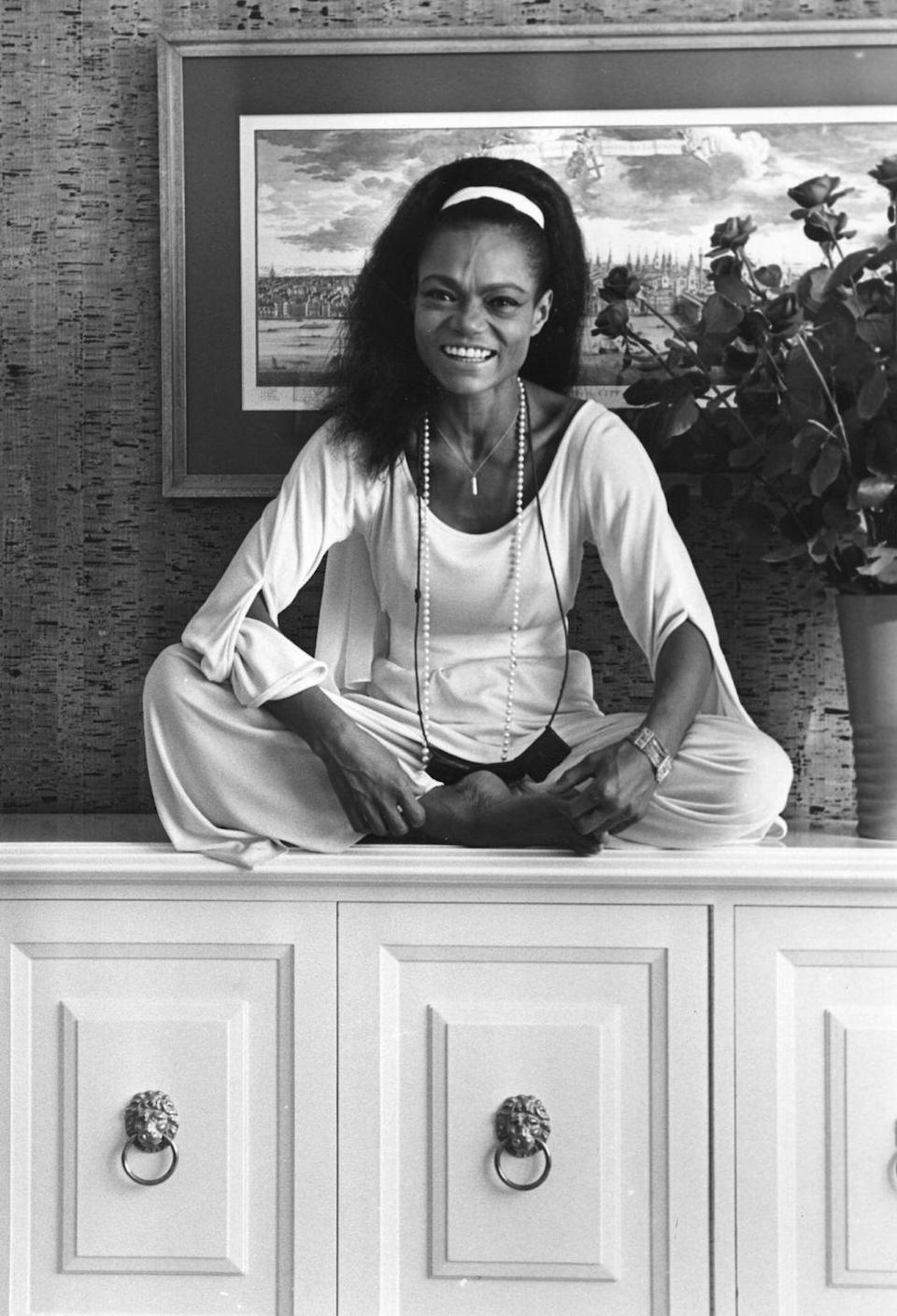 <p>Relaxed and happy, the dancer and singer lounges atop a console in a white top and matching pants, with her hair fixed in the classic teased style of that time.</p>
