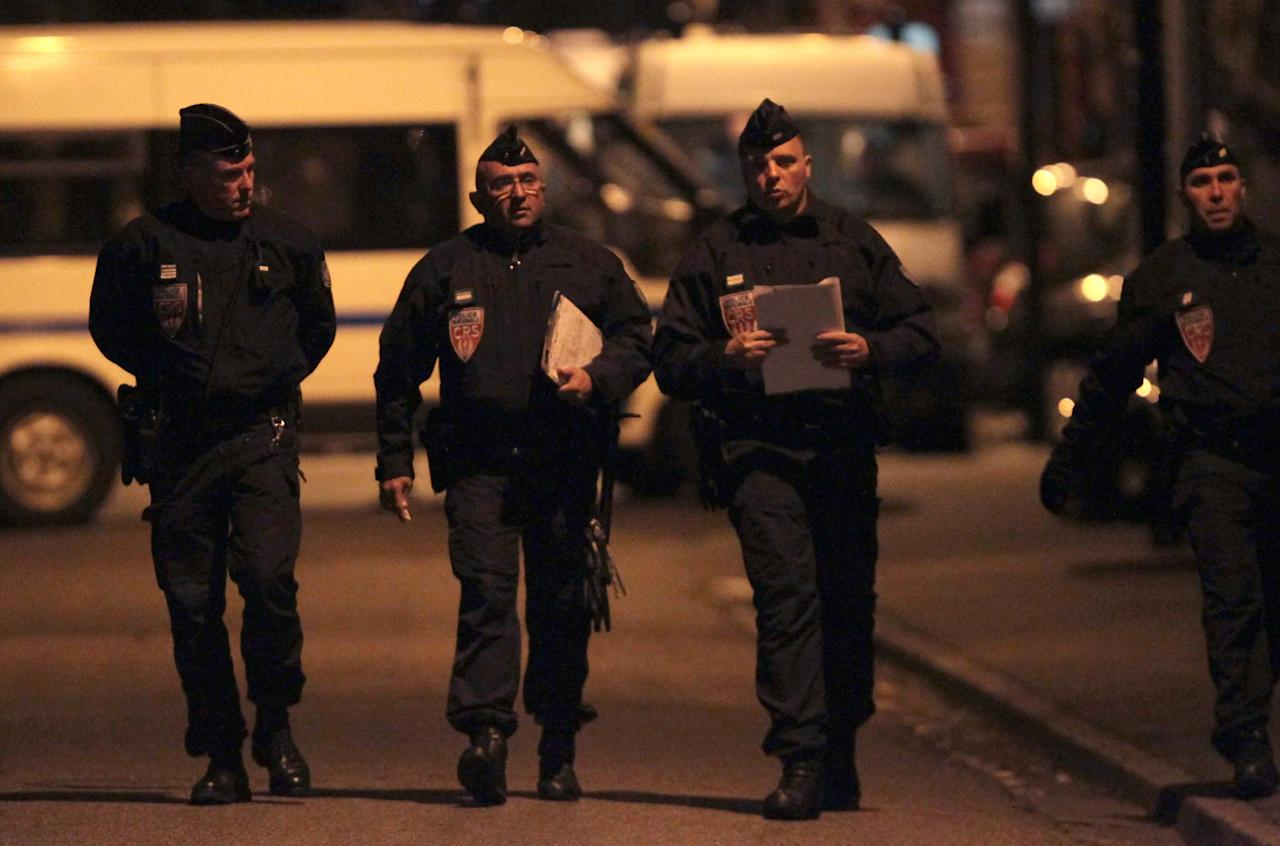 Police officers walk next to the building in Toulouse, France, Wednesday March 21, 2012 where a suspect in the shooting at the Ozar Hatorah Jewish school has been spotted. A father and his two sons were among four people who died Monday when a gunman opened fire in front of a Jewish school in the city in southwest France. (AP Photo/Bob Edme)