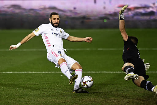 Real Madrid's Karim Benzema, left, scores past Athletic Bilbao's goalkeeper Unai Simon his side's first goal during Spanish Super Cup semi final soccer match between Real Madrid and Athletic Bilbao at La Rosaleda stadium in Malaga, Spain, Thursday, Jan. 14, 2021. (AP Photo/Jose Breton)