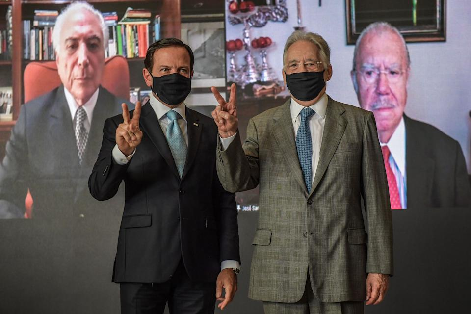 Sao Paulo's Governor Joao Doria (L) and former Brazilian President (1995-2003) Fernando Henrique Cardoso pose for pictures as they hold a video conference with former presidents (2016-2018) Michel Temer (L) and (1985-1990) Jose Sarney during an event in defence of life and to promote the importance of the vaccine against the novel coronavirus COVID-19, at Bandeirantes Palace in Sao Paulo, Brazil, on January 25, 2021. (Photo by Nelson ALMEIDA / AFP) (Photo by NELSON ALMEIDA/AFP via Getty Images)