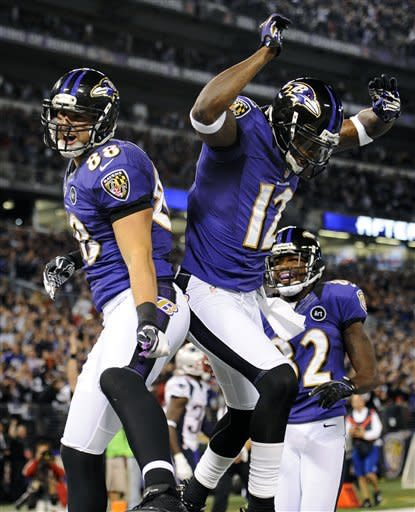 Baltimore Ravens tight end Dennis Pitta, left, celebrates his touchdown with teammates Jacoby Jones (12) and Torrey Smith, back, in the first half of an NFL football game against the New England Patriots in Baltimore, Sunday, Sept. 23, 2012. (AP Photo/Nick Wass)