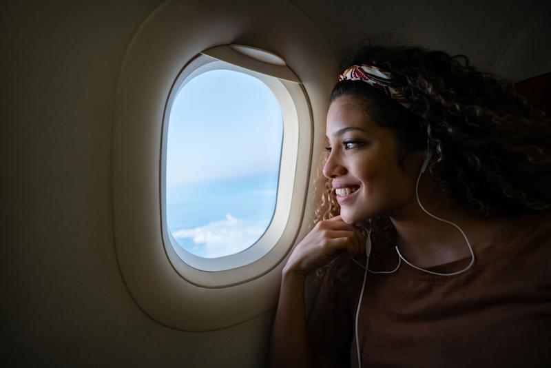 Portrait of a happy woman traveling by plane and listening to music with headphones while looking through the window - lifestyle concepts