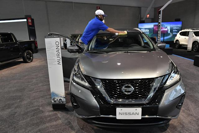 A worker readies a Nissan for exhibit at the 2020 New England Auto Show press preview at Boston Convention & Exhibition Center on 16 January, in Boston, Massachusetts. Photo: Paul Marotta/Getty Images