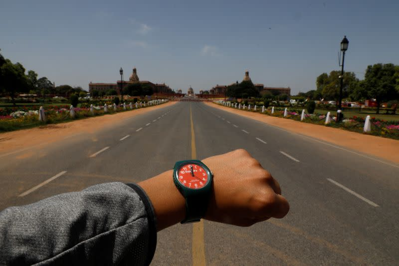 FILE PHOTO: A watch showing the time at noon, is displayed for a photo in front of an empty road at Rajpath, during the coronavirus disease (COVID-19) outbreak, in New Delhi