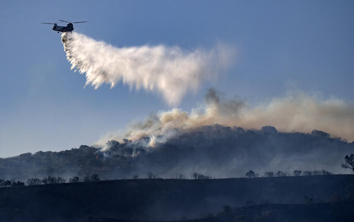 A helicopter drops retardant on the Silverado wildfire off Santiago Canyon Road where fierce winds have cause problems on Monday, Oct. 26, 2020, in Irvine, Calif. (Mindy Schauer/The Orange County Register via AP)