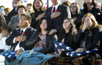 Family members of Chief Warrant Officer 2 Kirk T. Fuchigami Jr. look up as Apache helicopters fly over graveside services at Brigham City Cemetery, Monday, Dec. 9, 2019, in Brigham, Utah. From front, left to right: Kirk Fuchigami, father; Jana Lee Hunsaker Norman, mother-in-law; McKenzie Norman Fuchigami, wife; and Lisa Marie Casey, mother. United States Army pilot Fuchigami and his co-pilot died when their helicopter crashed Nov. 20 as they provided security for troops on the ground in eastern Logar Province outside of Kabul. Afghanistan. (Steve Griffin/The Deseret News via AP)