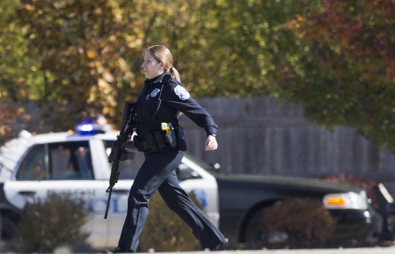 A police officer responds to a call of a shooting at the Azana Spa in Brookfield, Wis. Sunday, Oct. 21, 2012. Multiple people were wounded when someone opened fire at the spa near the Brookfield Square Mall. Deputies are still looking for the gunman. (AP Photo/Tom Lynn)