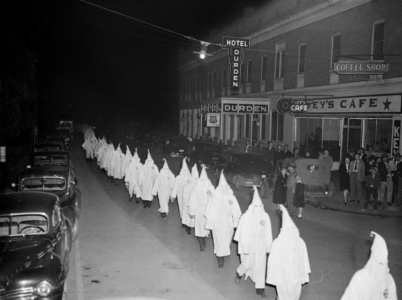 FILE -In this Feb. 3, 1948 file photo, members of the Ku Klux Klan, wearing traditional white hoods and robes, march in single file around the town square in Swainsboro, Ga., headed for a cross burning. Extremist groups are joining together with a shared goal for whites. A new Ku Klux Klan alliance formed in March 2017 has united chapters from around the country, and a consortium of organizations composed of white nationalists and white separatists is marking its first anniversary. Watchdog groups say white extremists typically can't work together because of jealousy and infighting. But leaders say they're united as never before. (AP Photo, File)