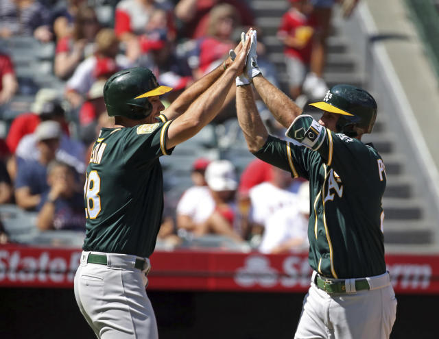 Oakland Athletics Stephen Piscotty, right, and Matt Olson celebrate as both score on Piscotty's home run against the Los Angeles Angels in the second inning of a baseball game in Anaheim, Calif., Sunday, Sept. 30, 2018. (AP Photo/Reed Saxon)