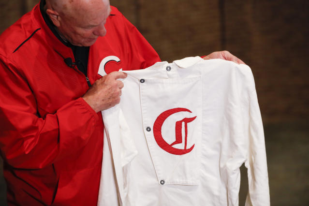 "Greg Rhodes, the Cincinnati Reds baseball team historian, holds a replica jersey of the early Cincinnati Red Stockings team at Cincinnati Reds Hall of Fame, Tuesday, Jan. 8, 2019, in Cincinnati. The Reds will play games in 15 sets of throwback uniforms, including navy blue and a ""Palm Beach"" style, during a season-long celebration of the 1869 Red Stockings who pioneered professional baseball. (AP Photo/John Minchillo)"