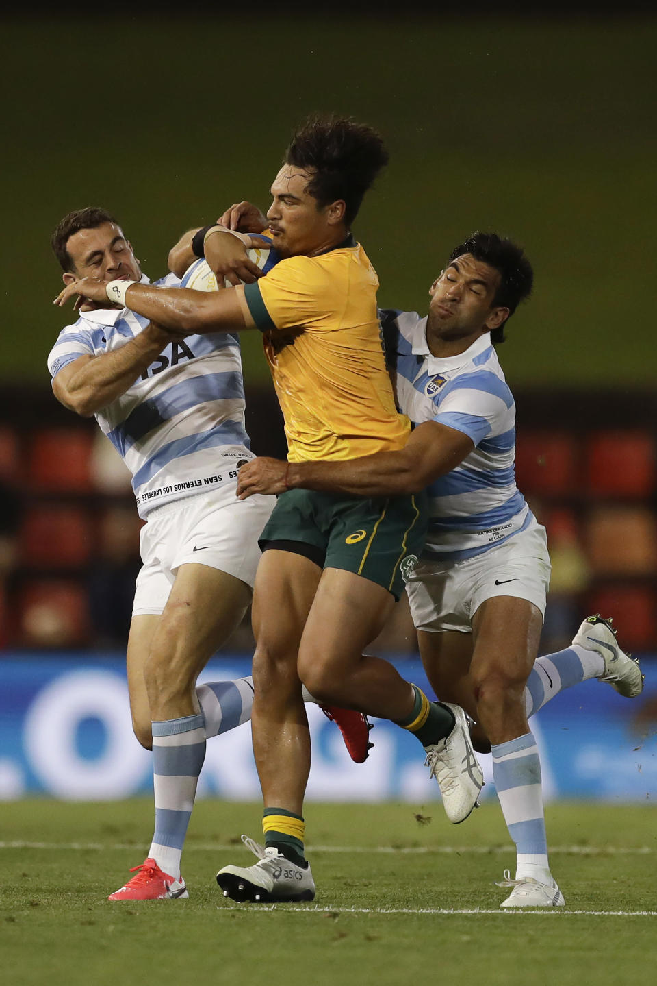 Australia's Jordan Petaia, center, is tackled by Argentina's Emiliano Boffelli, left, and Argentina's Matias Orlando, right, during their Tri-Nations rugby union match in Newcastle, Australia, Saturday, Nov. 21, 2020. (AP Photo/Rick Rycroft)