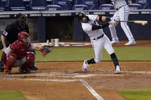 Miami Marlins' Miguel Rojas, right, singles during the fourth inning of a baseball game against the Philadelphia Phillies, Monday, Sept. 14, 2020, in Miami. Phillies catcher Rafael Marchan, front left, looks on. (AP Photo/Lynne Sladky)