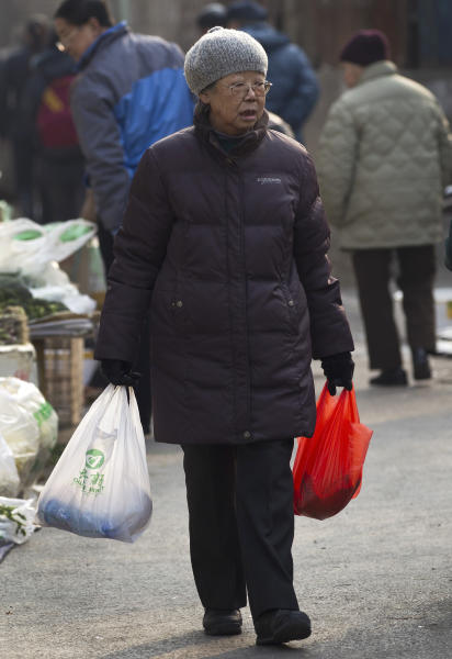 An elderly Chinese woman carries plastic bags of groceries she bought at a morning market in Beijing Friday, March 9, 2012. China's inflation fell sharply in February, giving Beijing more leeway to stimulate its slowing economy. Inflation in politically sensitive food costs declined even more markedly, falling to 6.2 percent from the previous month's 10.5 percent. (AP Photo/Andy Wong)