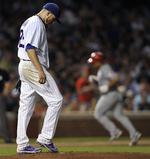 Chicago Cubs' Matt Garza left, reacts as Cincinnati Reds' Xavier Paul rounds the bases after his three-run home run during the sixth inning of a baseball game Tuesday, June 11, 2013, in Chicago. (AP Photo/Jim Prisching)