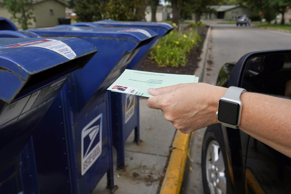 FILE - In this Aug. 18, 2020, file photo, a person drops applications for mail-in-ballots into a mailbox in Omaha, Neb. U.S. Postal Service records show delivery delays have persisted across the country as millions of Americans began voting by mail, raising the possibility of ballots being rejected because they arrive too late. Postal data covering the beginning of October show nearly all of the agency's delivery regions missing agency targets of having more than having more than 95% of first-class mail arrive within five days. (AP Photo/Nati Harnik, File)