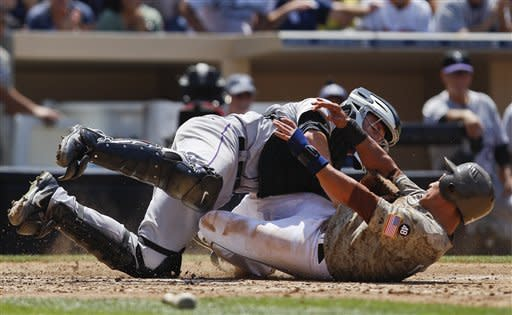 San Diego Padres' Everth Cabrera, bottom, slides hard into Colorado Rockies catcher Jordan Pacheco while scoring on a single by John Baker during the fourth inning of a baseball game on Sunday, July 22, 2012, in San Diego. (AP Photo/Lenny Ignelzi)