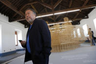 """Dissident Chinese artist Ai Weiwei walks by his work """"Life Cycle"""", a migrants' boat made of bamboo, during a press preview of his new exhibition """"Rapture"""" in Lisbon, Thursday, June 3, 2021. The world-renowned artist is putting on the biggest show of his career, and he is doing it in a place he's fallen in love with: Portugal. (AP Photo/Armando Franca)"""