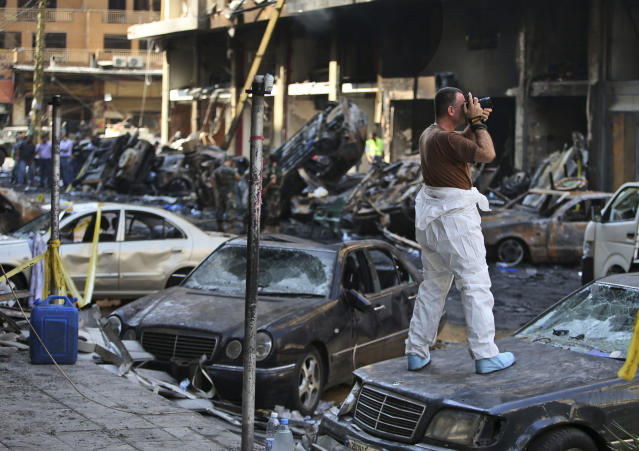A Lebanese army investigator takes photos at the site of a car bomb explosion in southern Beirut, Lebanon, Friday, Aug. 16, 2013. A powerful car bomb tore through a bustling south Beirut neighborhood that is a stronghold of Hezbollah on Thursday, killing at least 18 and trapping dozens of others in an inferno of burning cars and buildings in the bloodiest attack yet on Lebanese civilians linked to Syria's civil war. (AP Photo/Hussein Malla)