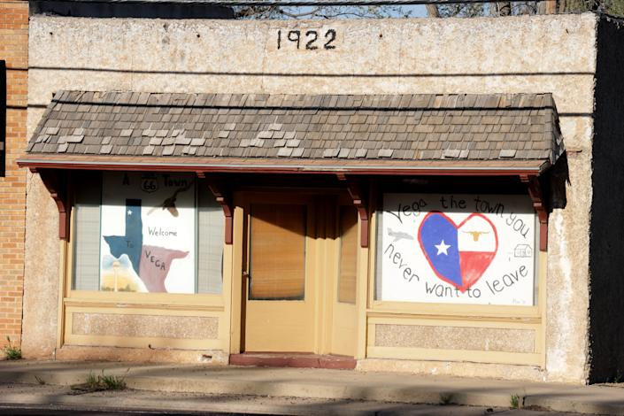 Signs in the window of a Vega, TX business. Some businesses closed in mid-March after the pandemic hit. The town's several restaurants started doing takeout only. The grocery store locked its doors and began doing pick up or delivery only.