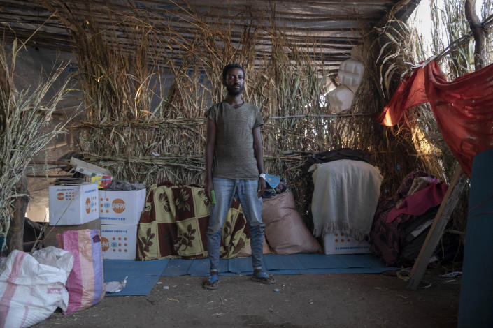 """Samir Beyen, 26, a survivor from Mai-Kadra, Ethiopia, stands inside his shelter at Umm Rakouba refugee camp in Qadarif, eastern Sudan, Nov. 25, 2020. Witnesses say hundreds of civilians were slaughtered in Mai-Kadra, but they disagree about who killed whom. """"It was like the end of the world,"""" recalled Beyen, a mechanic, who said he was stopped and asked if he was Tigrayan, then beaten and robbed. He said he saw people being slaughtered with knives, and dozens of rotting corpses. """"We could not bury them because the soldiers were near,"""" he said. Some witnesses said Ethiopian federal and Amhara regional troops attacked Tigrayans, while others say it was Tigrayan forces and their allies who targeted Amhara. (AP Photo/Nariman El-Mofty)"""