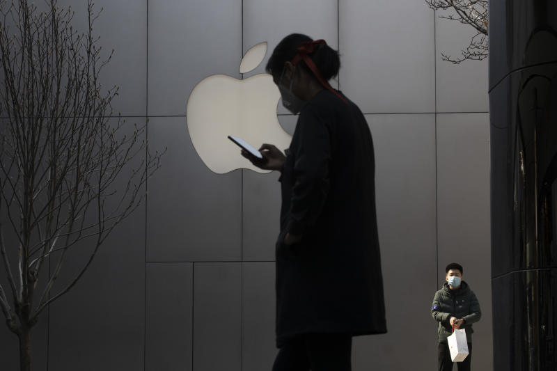In this Feb. 26, 2020, photo, a woman uses her phone near the Apple store in Beijing. In a lively Muslim quarter of Nanchang city in eastern China, a sprawling Chinese factory turns out computer screens, cameras and fingerprint scanners for a supplier to international tech giants such as Apple and Lenovo. (AP Photo/Ng Han Guan)