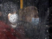 People wearing a face mask to protect against coronavirus sit on a bus in Belgrade, Serbia, Monday, Jan. 11, 2021. A spate of rainy and snowy weather across the Balkans in the past days has left homes and fields flooded, disrupted road and sea traffic and caused power outages. (AP Photo/Darko Vojinovic)