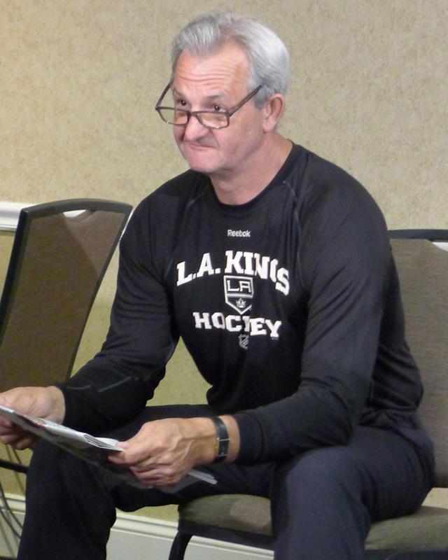 Coach Darryl Sutter looks up from reading the paper before his media availability at a hotel adjacent to the Kings' practice facility in El Segundo, Calif., on Friday, June 6, 2014. (AP Photo/The Canadian Press, Neil Davidson)