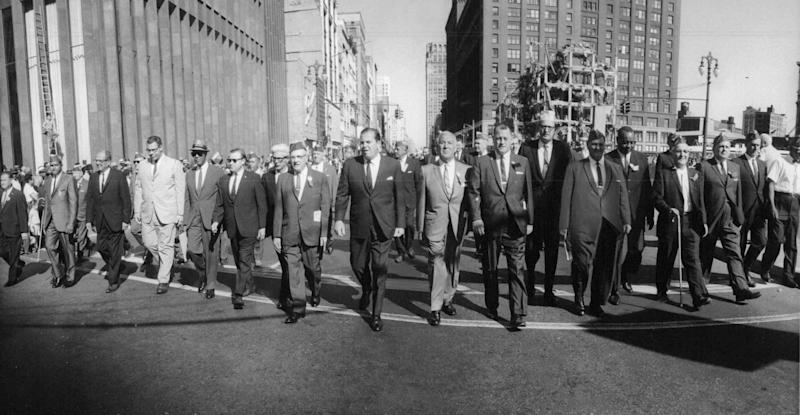 The march of the high command. Led by Walter Reuther, fifth from left and Mayor Jerome Cavanagh. A flying wedge of labor's chieftains strides down Woodward on September 5, 1966.
