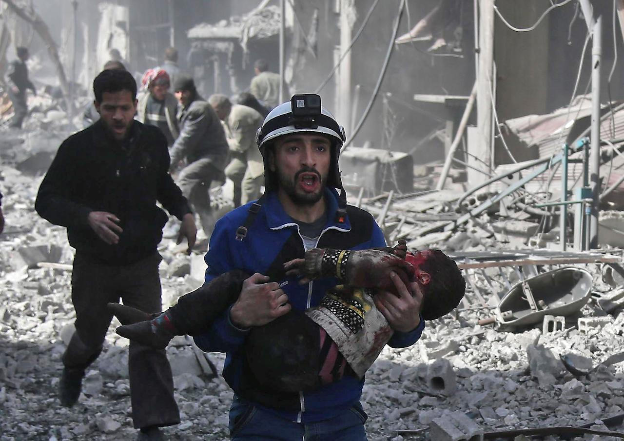 <p>A Syrian civil defence member carries an injured child rescued from between the rubble of buildings following government bombing in the rebel-held town of Hamouria, in the besieged eastern Ghouta region on the outskirts of the capital Damascus, on Feb. 19, 2018. (Photo: Abdulmonam Eassa /AFP/Getty Images) </p>