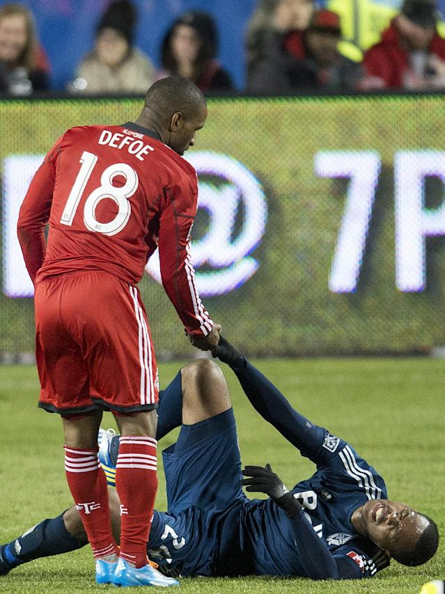 Toronto FC forward Jermain Defoe (18) tries to help up Vancouver Whitecaps defender Carlyle Mitchell, right, during second half semi-final Amway Canadian Championship soccer action in Toronto on Wednesday, May 7, 2014. (AP Photo/The Canadian Press, Nathan Denette)