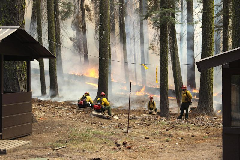 In this photo provided by the U.S. Forest Service, fire crew members stand watch near a controlled burn operation intended to protect the Yosemite Institute educational center as they fight the Rim Fire in Yosemite National Park in California Sunday, Sept. 1, 2013. The massive wildfire is now 75 percent contained according to a state fire spokesman. (AP Photo/U.S. Forest Service, Mike McMillan)