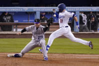 Los Angeles Dodgers' Justin Turner, right, is safe at first as Colorado Rockies first baseman C.J. Cron is unable to field the throw during the third inning of a baseball game Tuesday, April 13, 2021, in Los Angeles. (AP Photo/Mark J. Terrill)