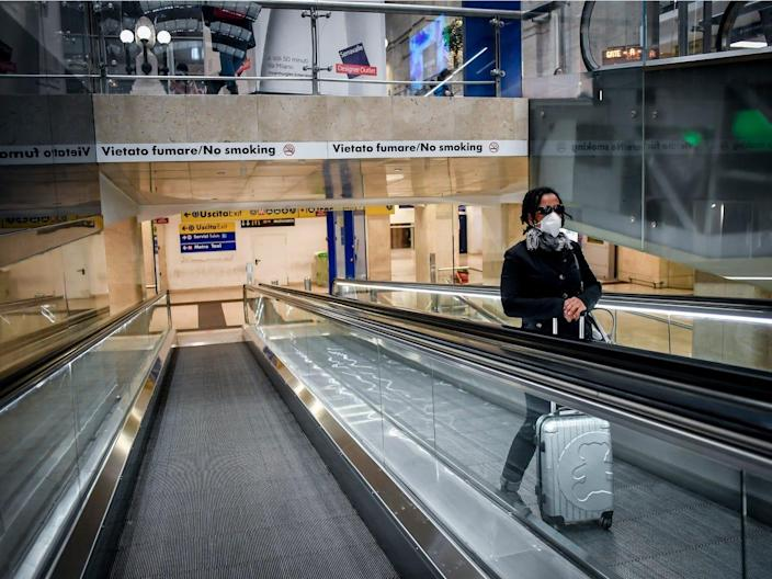 A person wears a mask on an escalator inside Central train station, in Milan, Italy.