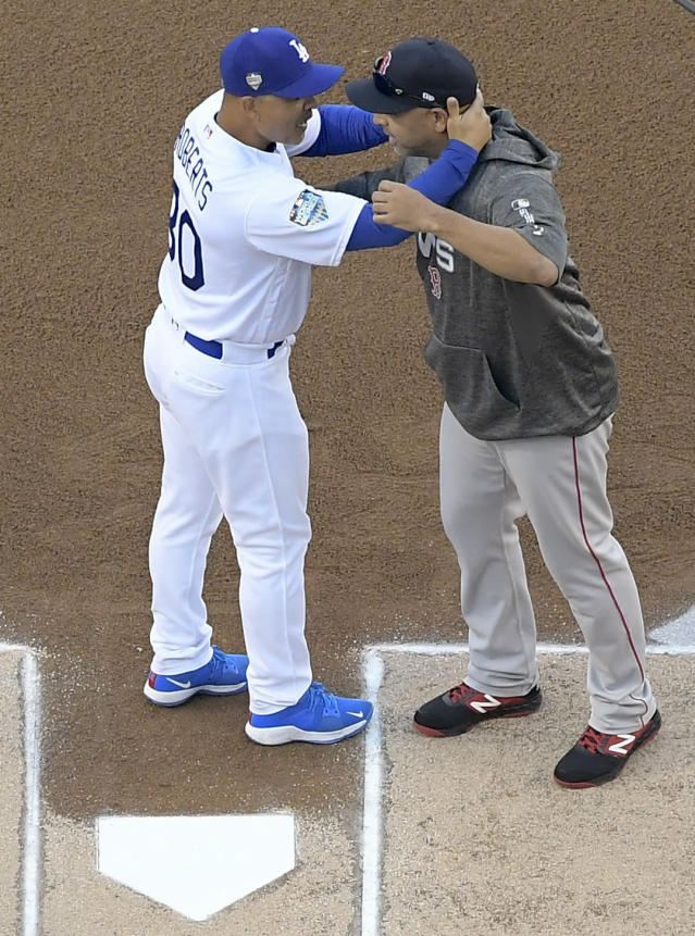 Los Angeles Dodgers manager Dave Roberts and Boston Red Sox manager Alex Cora hug before Game 3 of the World Series baseball game on Friday, Oct. 26, 2018, in Los Angeles. (AP Photo/Mark J. Terrill)