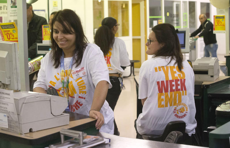 Cashiers of a do-it-yourself store wear shirts to protest against last week's court decision to force shorter working hours on Sundays, in Gennevilliers, France, north of Paris, Sunday Sept. 29, 2013. Employees at two big home-improvement retailers are putting pressure on France's government to let their stores stay open on Sundays. (AP Photo/Michel Euler)
