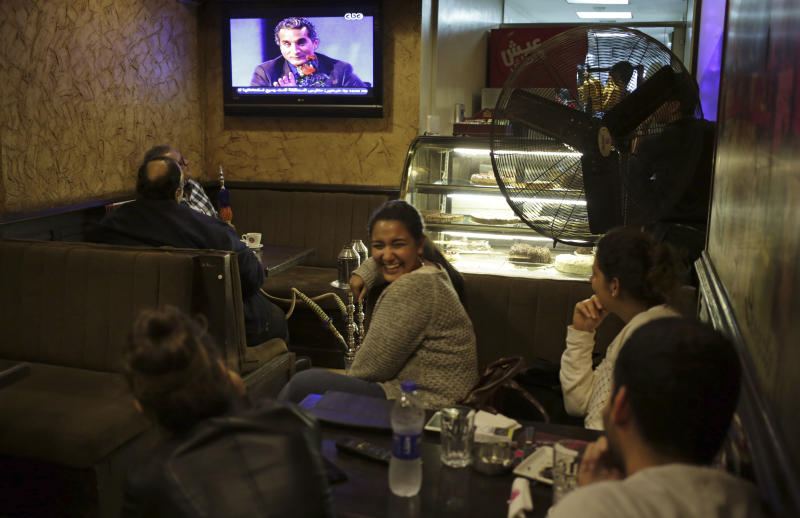 "Egyptians watch the weekly program of Bassem Youssef, the man known as ""Egypt's Jon Stewart,"" at a coffee shop in Cairo, Egypt, Friday, Oct. 25, 2013. Egypt's most popular TV satirist, famed for mercilessly skewering the former Islamist president on his weekly program, dove headfirst back into stormy politics Friday after four months off the air amid the turmoil surrounding the country's coup. His new target for mockery: the over-the-top pro-military fervor sweeping Egyptians. Youssef returned to the air in a radically different nation, where satirizing the leadership is a far trickier task. (AP Photo/ Khalil Hamra)"