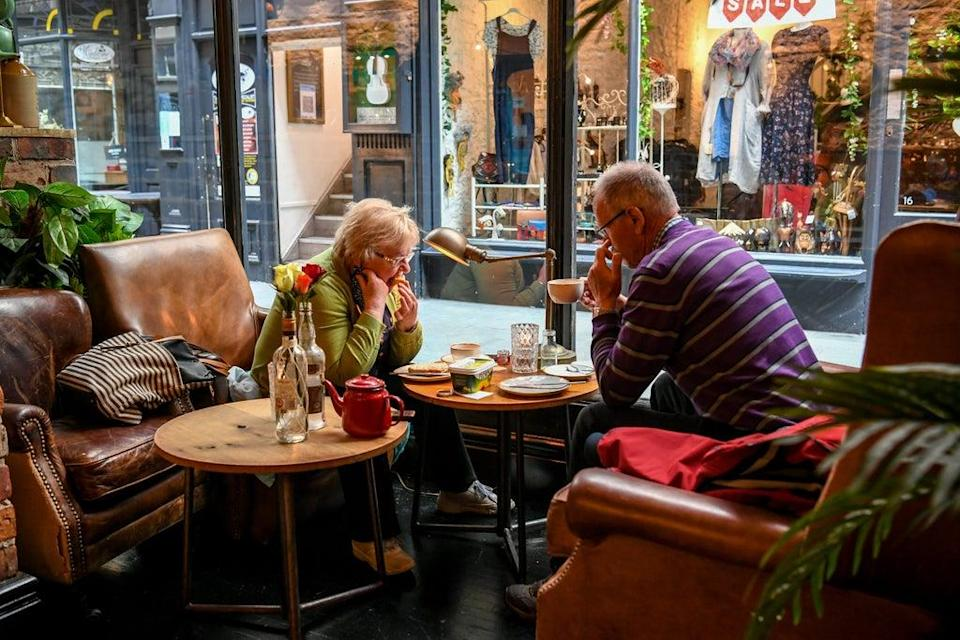 People enjoy a breakfast and coffee in Cardiff (PA) (PA Wire)