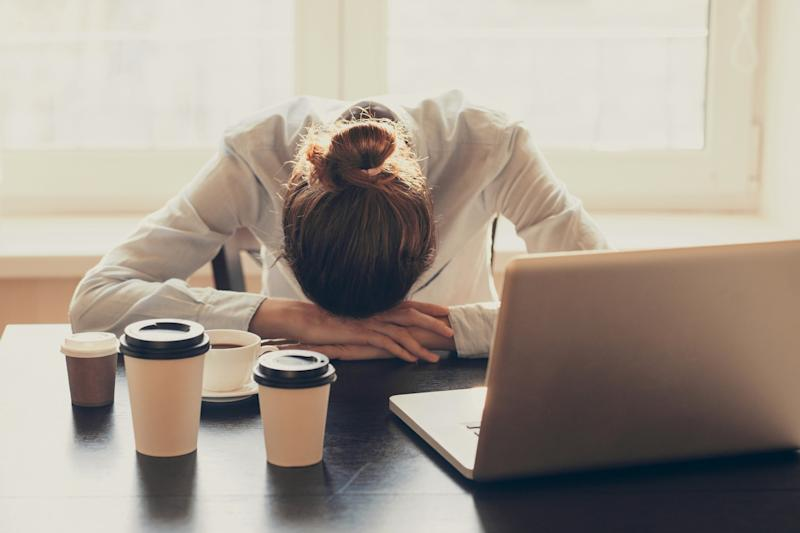 Tired woman with empty coffee cups