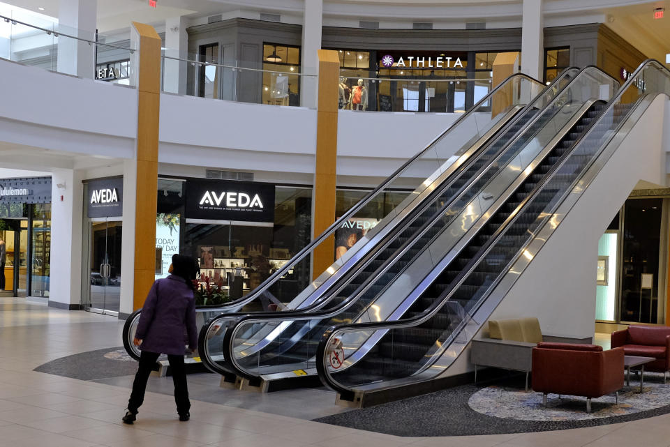 A visitor looks down an empty hallway at The Fashion Mall at Keystone, Wednesday, March 18, 2020, in Indianapolis. Simon Property Group, the largest owner of shopping malls in the nation, is closing all of its malls and retail properties because of the coronavirus outbreak. (AP Photo/Darron Cummings)