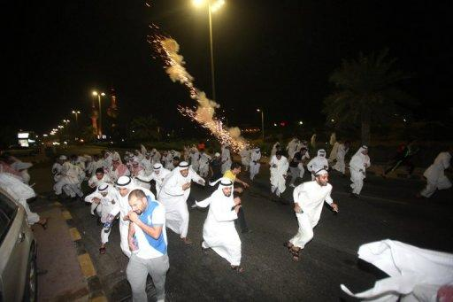 Kuwaiti opposition supporters run for cover during a protest in Kuwait City last month against the decision by Emir Sheikh Sabah al-Ahmad al-Sabah to amend the electoral law despite it having been confirmed by a court in September