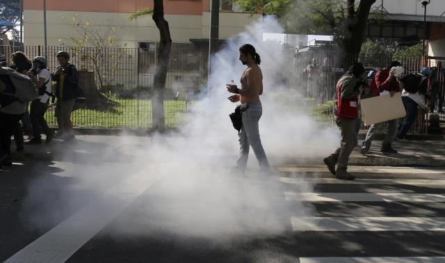 A demostrator walks near to tear gas fired by mlitary police at demostrators near Caarao metro station during a protest against the 2014 World Cup, in Sao Paulo June 12, 2014. REUTERS/Nacho Doce (BRAZIL - Tags: SPORT SOCCER WORLD CUP POLITICS CIVIL UNREST)