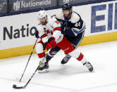 Carolina Hurricanes forward Vincent Trocheck, left, controls the puck against Columbus Blue Jackets defenseman Vladislav Gavrikov during the second period of an NHL hockey game in Columbus, Ohio, Sunday, Feb. 7, 2021. (AP Photo/Paul Vernon)