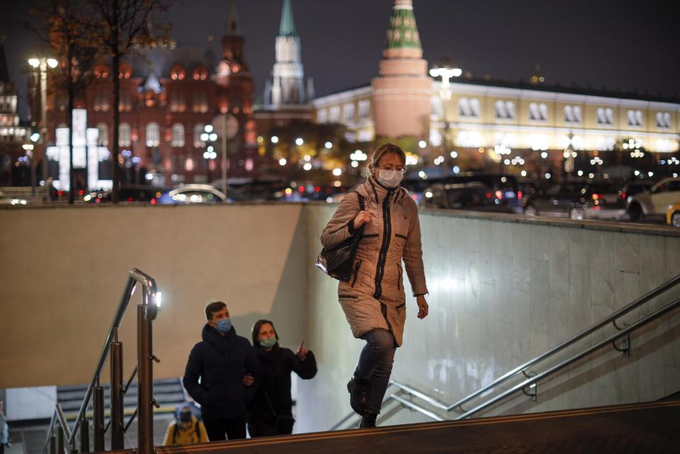 A woman wearing a face mask to help curb the spread of the coronavirus walks from the underpass under the street with the Historical Museum and the Kremlin are in the background in Moscow, Russia, Tuesday, Nov. 3, 2020. Russia reported more than 18,000 daily coronavirus cases for a record five straight days. However, authorities have resisted a second lockdown or shutting down businesses despite reports about overwhelmed hospitals, drug shortages and inundated medical workers. (AP Photo/Alexander Zemlianichenko)