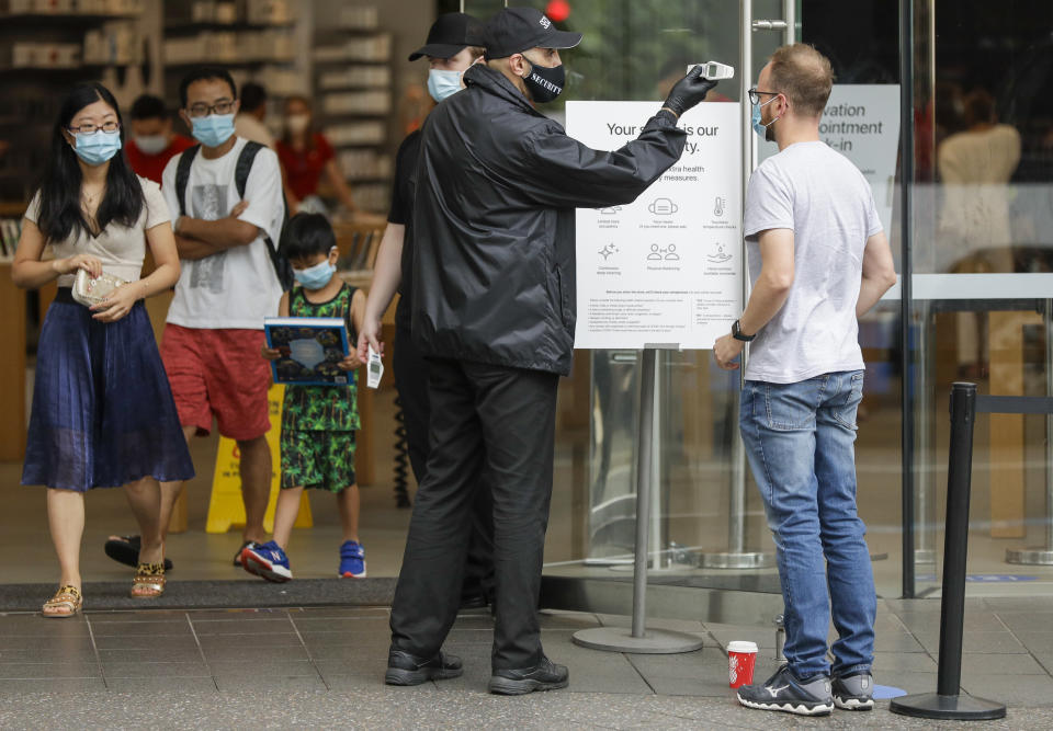 A security guard takes the temperature of a customer at a shopping precinct in Sydney. Source: AAP