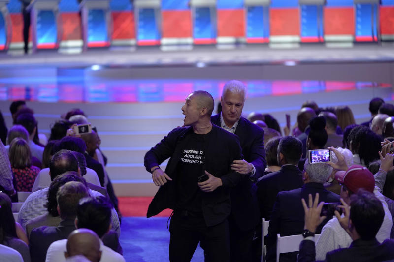 A protester is removed Sept. 12, 2019, after interrupting a Democratic presidential primary debate hosted by ABC at Texas Southern University in Houston. | David J. Phillip—AP