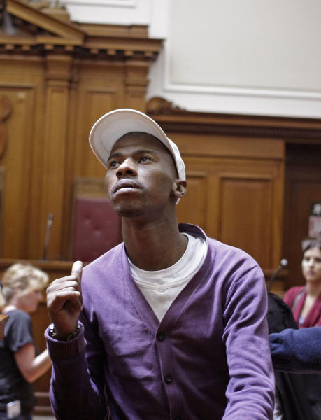 "Xolile Mngeni, shows his family members a thumbs up after being sentenced in court at Cape Town, South Africa, Wednesday, Dec. 5, 2012. A South African judge sentenced the triggerman in the 2010 honeymoon slaying of a Swedish bride to life in prison Wednesday, calling the shooter ""a merciless and evil person"" who deserved the maximum punishment for his crime. Prosecutors say the newlywed's British husband orchestrated the November 2010 killing. Judge Robert Henney did not hold back his contempt while sentencing Xolile Mngeni for the killing of 28-year-old Anni Dewani. Henney said that the shooter showed no remorse. (AP Photo/Schalk van Zuydam)"
