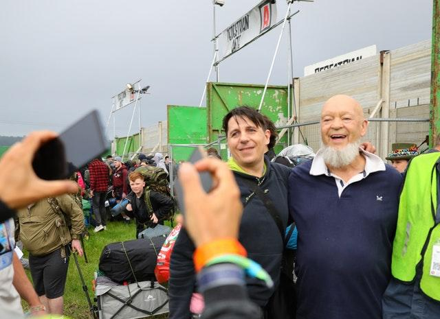 Festival organiser Michael Eavis takes pictures with fans as people arrive on the first day of the Glastonbury Festival at Worthy Farm in Somerset