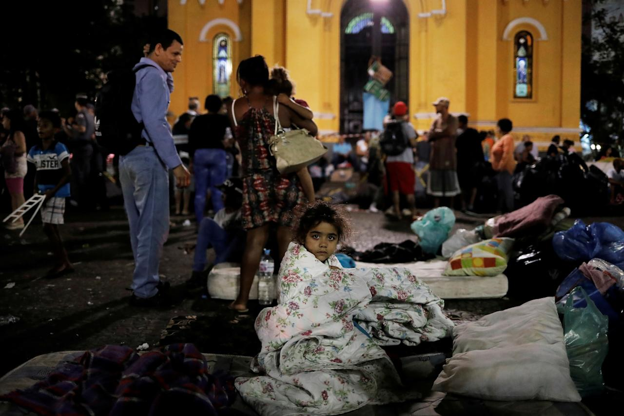 <p>A girl from a homeless family, that was living in the building that caught on fire, sits on her mattress donated by well-wishers in front of a church at Largo do Paissandu Square in Sao Paulo, Brazil, May 2, 2018. (Photo: Nacho Doce/Reuters) </p>